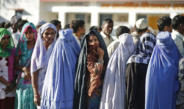 Muslim women stand in a queue to cast their votes at polling station in Palra village in Muzaffarnagar